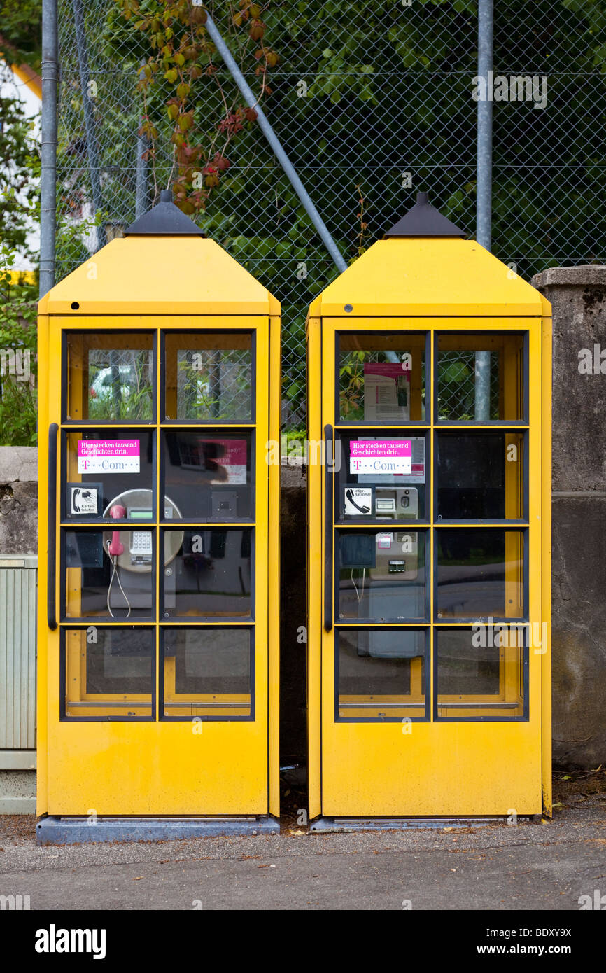 Two yellow telephone kiosks boxes Germany Europe - Stock Image