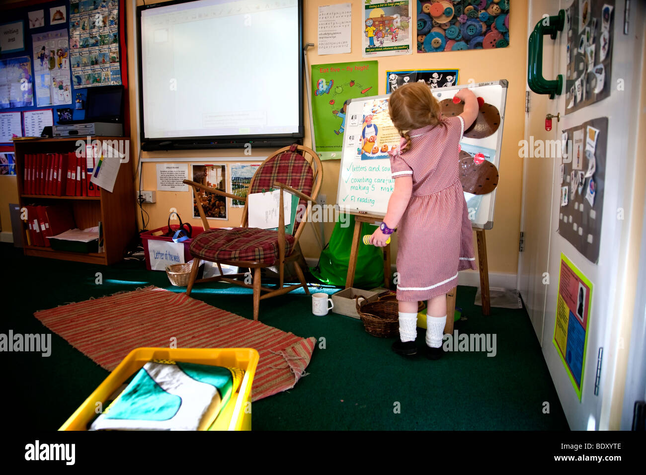 4 year old girl at whiteboard in foundation stage classroom in uk primary school - Stock Image