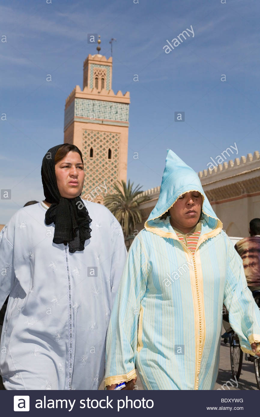 Two Arabic women in traditional dress walk in front of Moulay El Yazid Mosque in Marrakech, Morroco Stock Photo