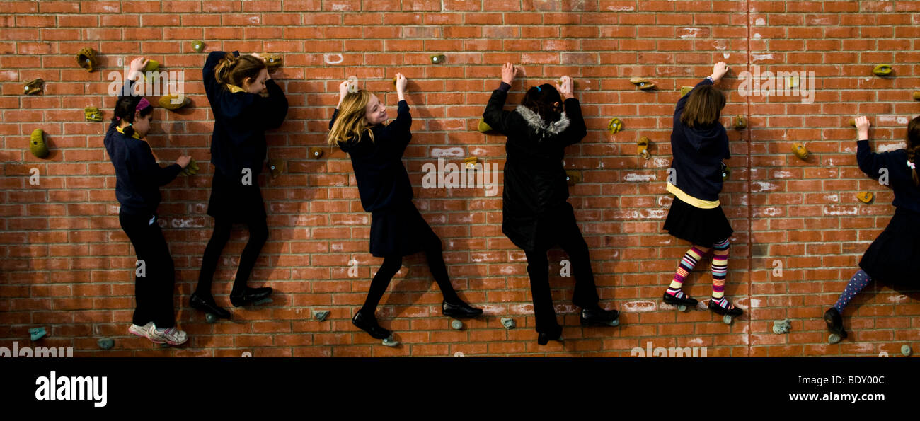 School children playing on a climbing wall - Stock Image
