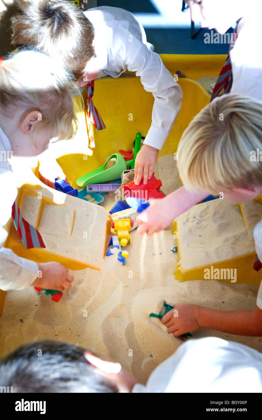 Foundation stage children playing in a sandpit - Stock Image