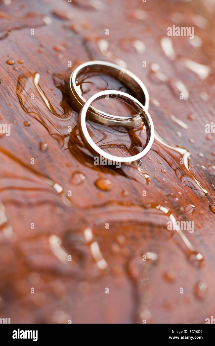 A pair of gold wedding rings on a wet polished wood surface - Stock Image