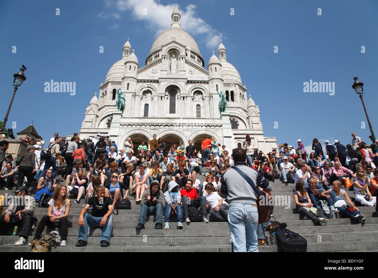 Tourists listen to a street entertainer on the steps before Sacre Coeur, Paris, France Stock Photo