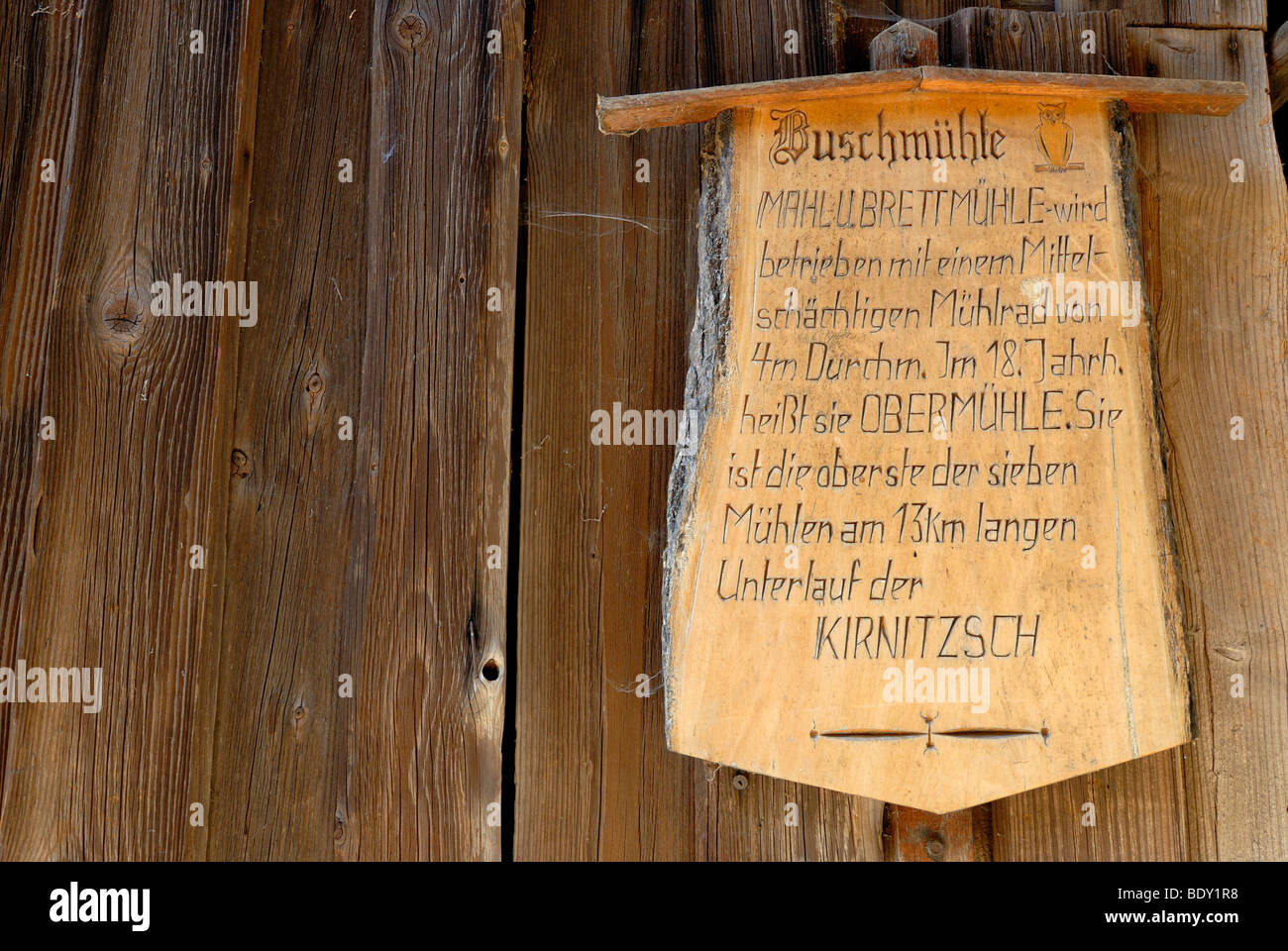 Wooden sign with information on the Buschmuehle mill on wooden wall, Kirnitzschtal valley, Nationalpark Saechsische - Stock Image