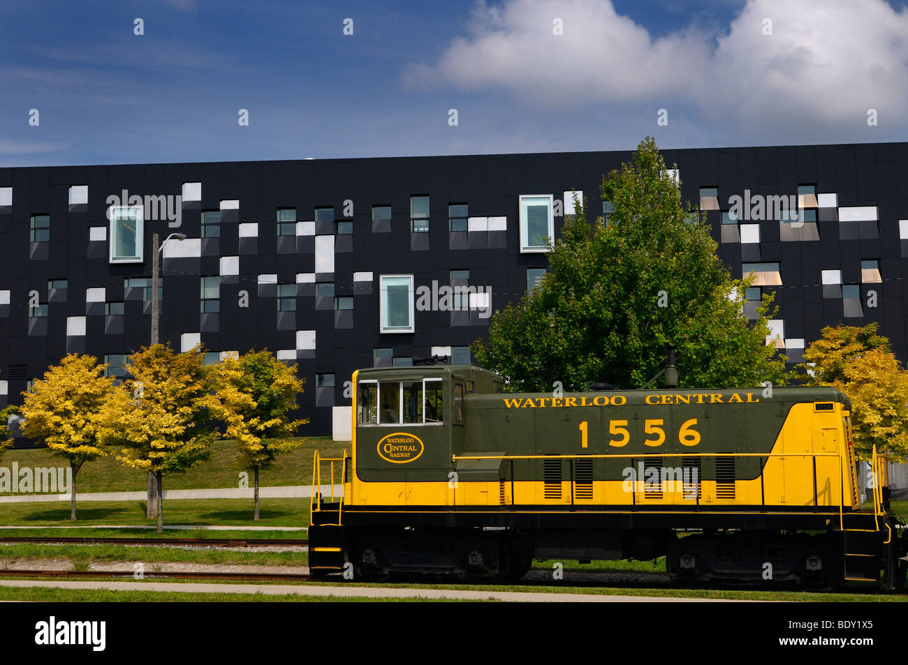 Yellow green historic Waterloo Central Railway train car with modern Perimeter Institute theoretical physics building - Stock Image