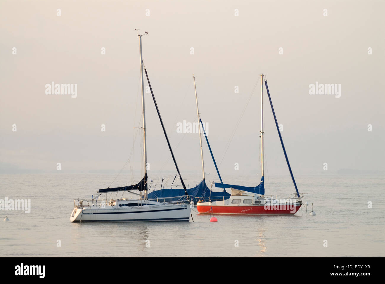 The first light of the day hits sailing boats in front of thick morning fog at Ammersee lake near Schondorf, Bavaria, Stock Photo