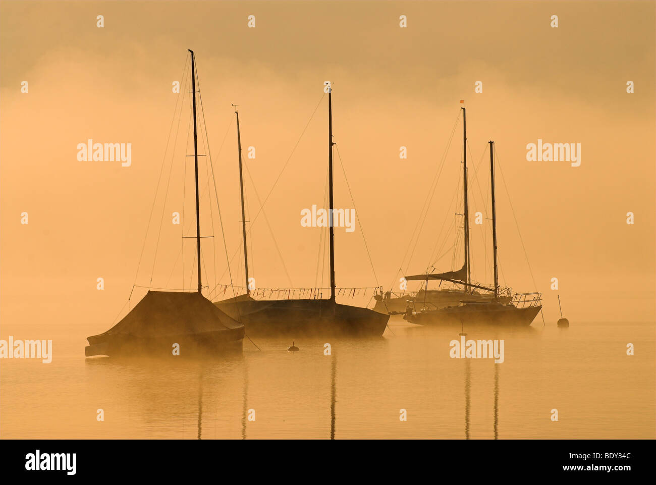 Morning fog above Lake Starnberg and silhouettes of boats at Seeshaupt, Bavaria, Germany, Europe Stock Photo