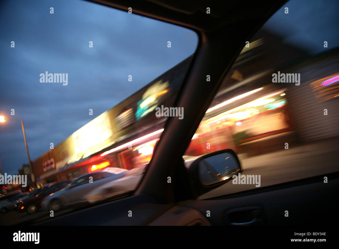 Car at night going down the road. Blurred city lights outside window. - Stock Image