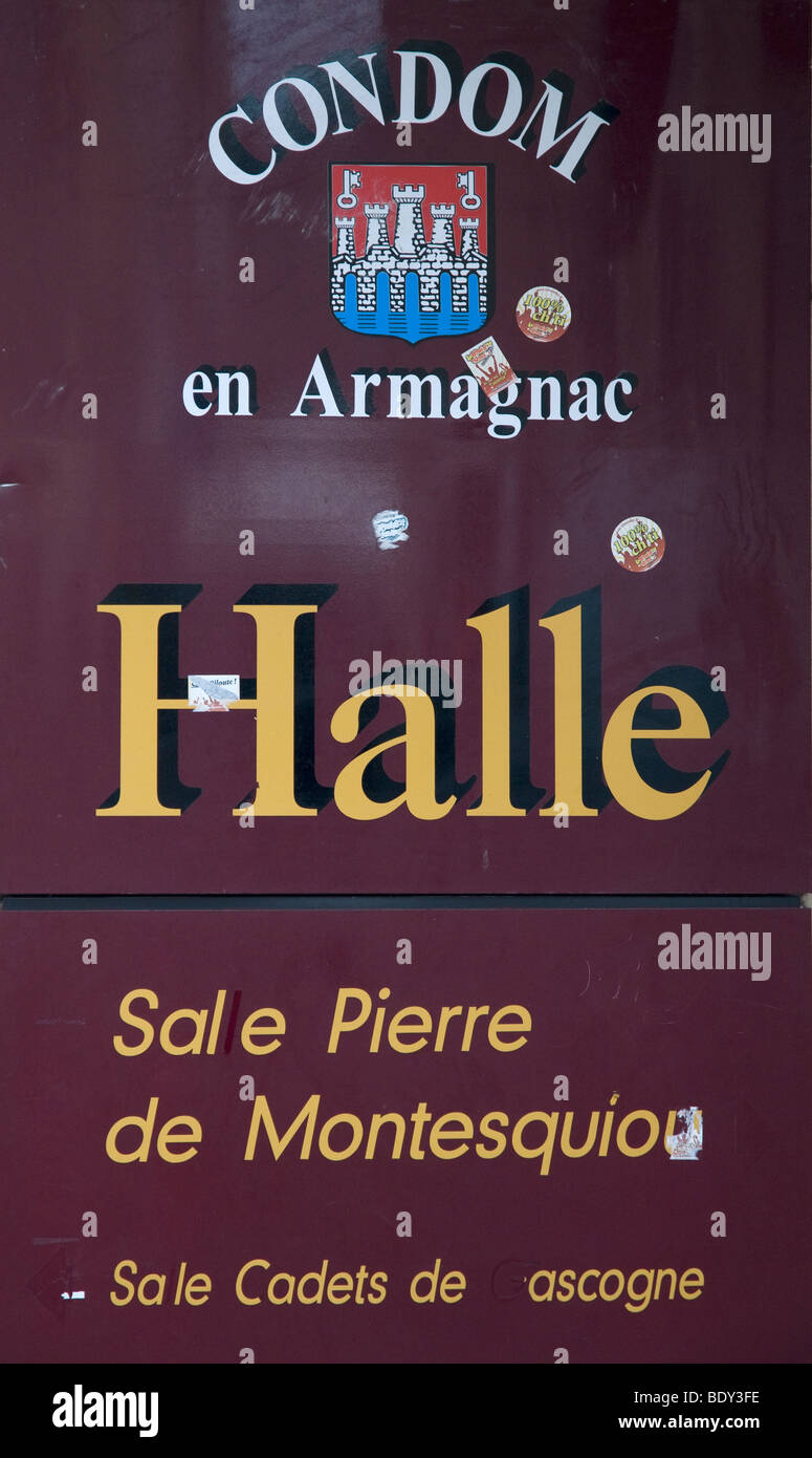 A sign outside the covered market of medieval Condom promotes the region's Armagnac; the town lies within the - Stock Image