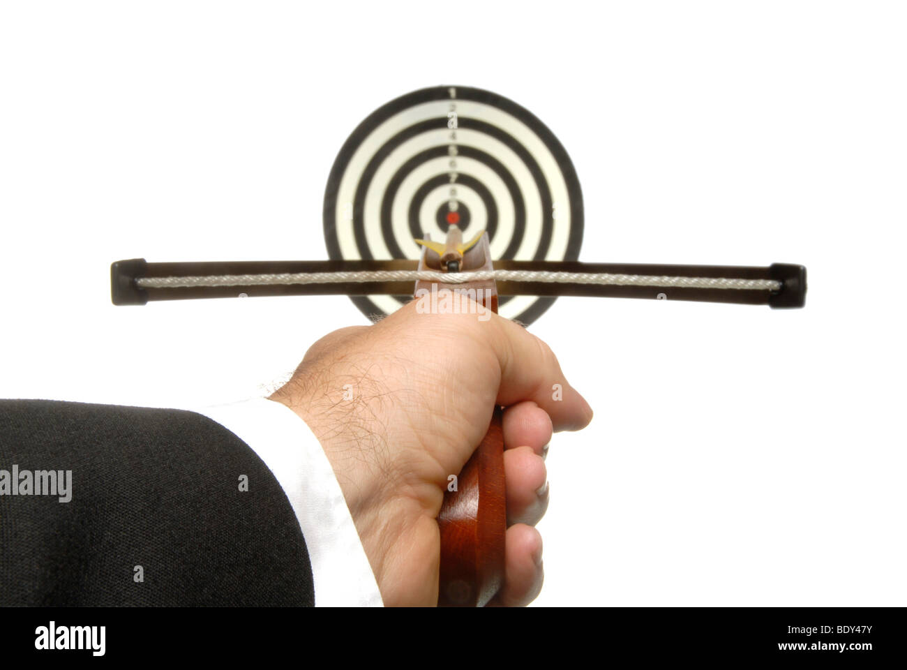 Business man with a crossbow aiming at a target - Stock Image