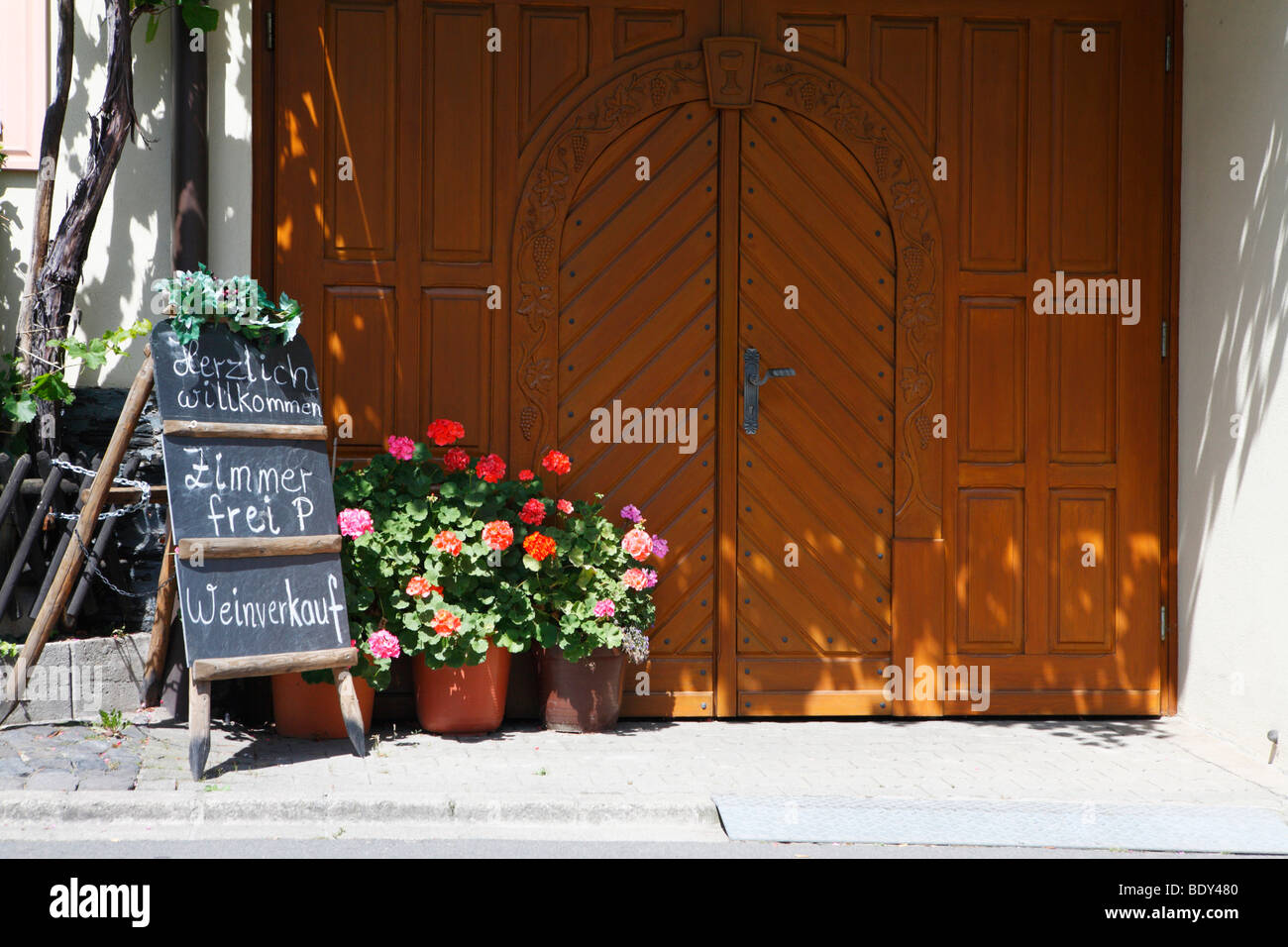 Old wooden door in Kues with a sign for room rental and wine sales, Bernkastel-Kues, Rhineland-Palatinate, Germany, - Stock Image