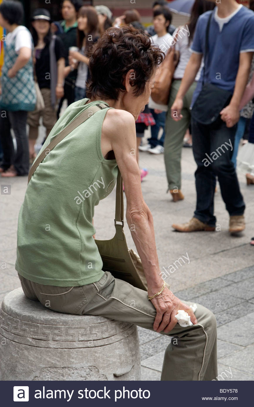 female person with anorexia symptoms resting in public pedestrian area - Stock Image