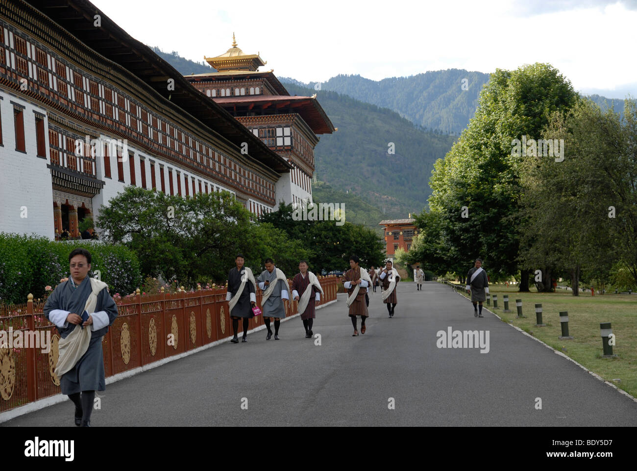 Traditionally dressed government employees leaving Thimphu Dzong in the late afternoon - Stock Image