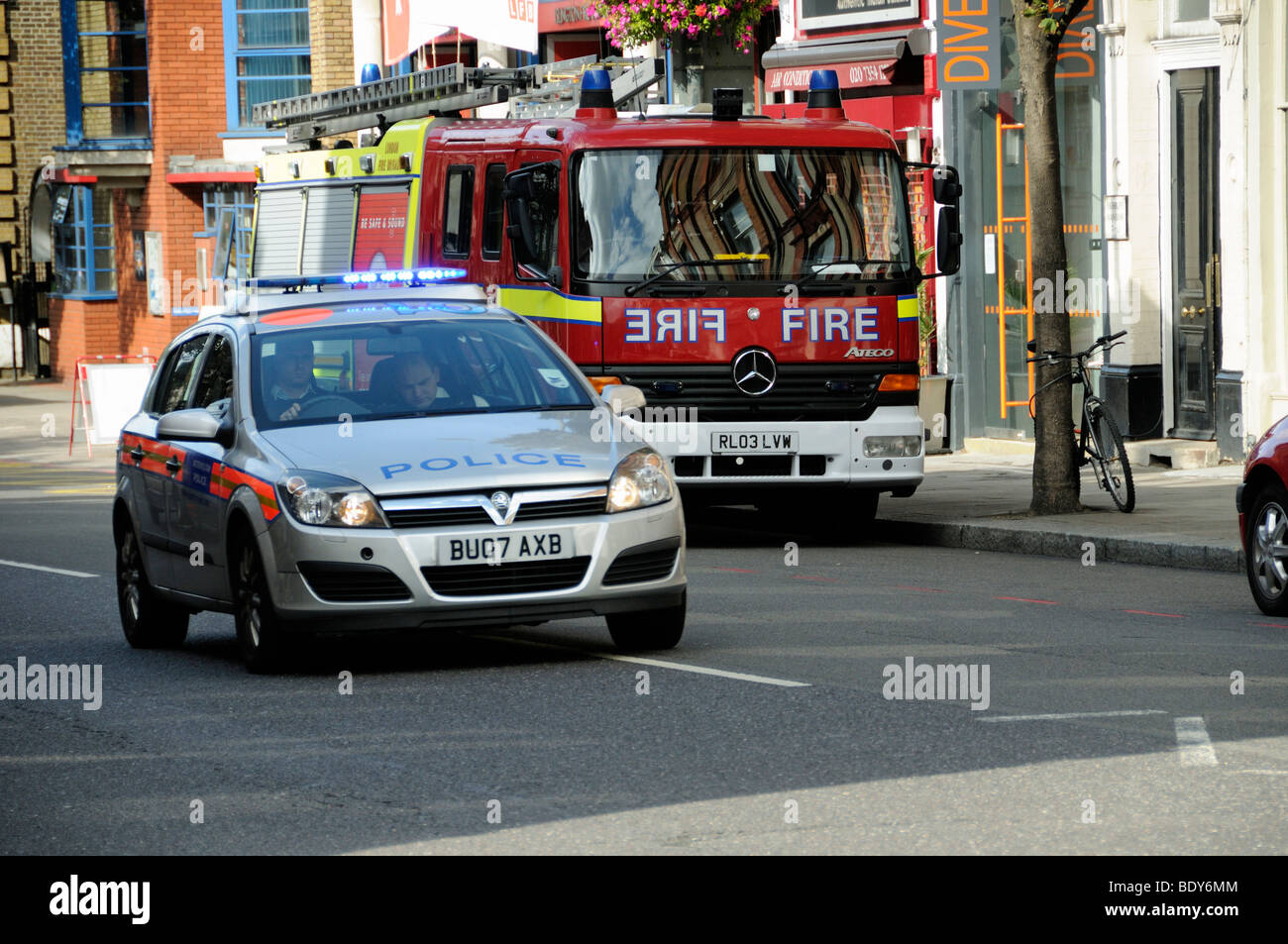police car with flashing lights passing fire engine, upper street