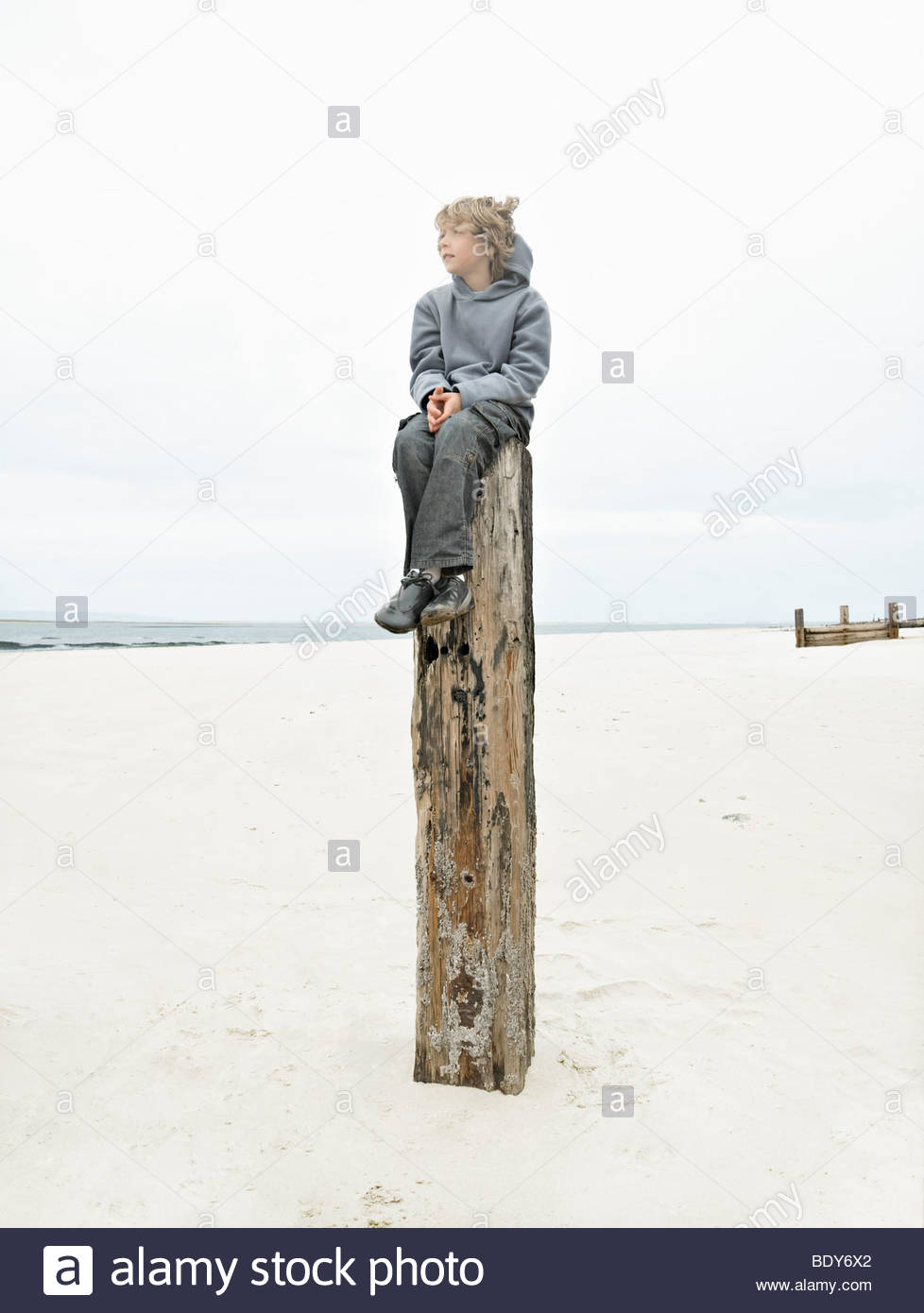 Boy sitting on top of post - Stock Image
