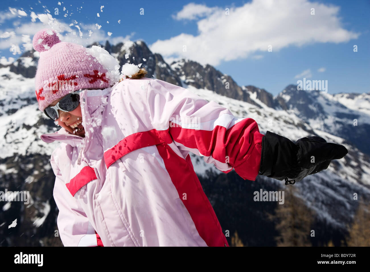 Girl in pink hit by snowball. - Stock Image