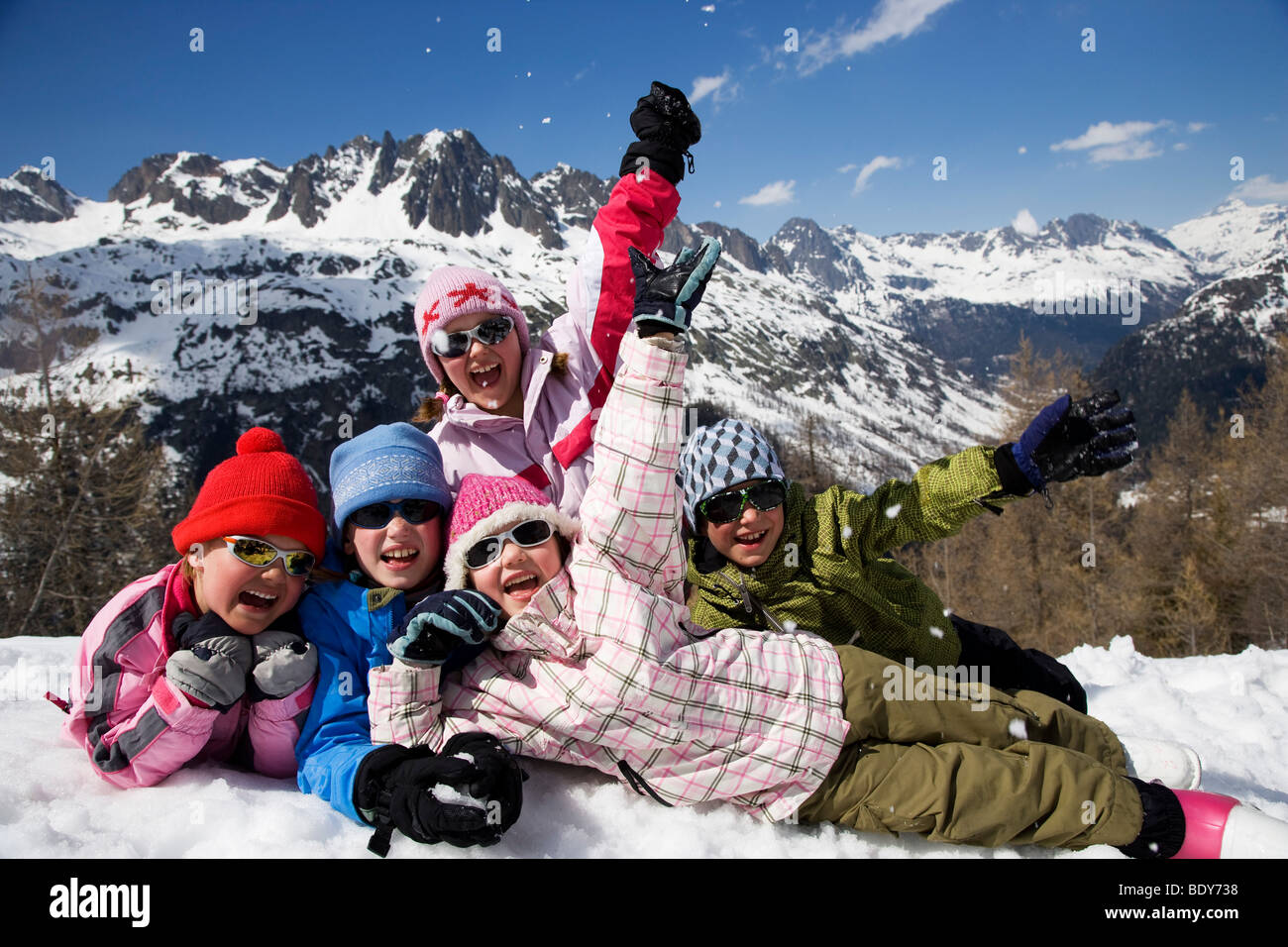 5 kids lying in the snow. Stock Photo