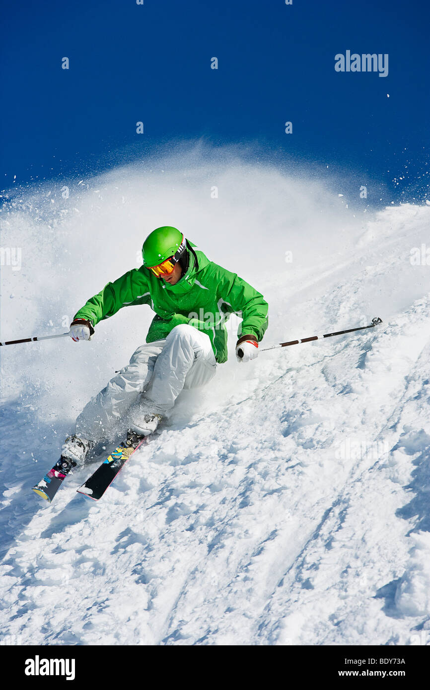 Man in green carving off piste. - Stock Image