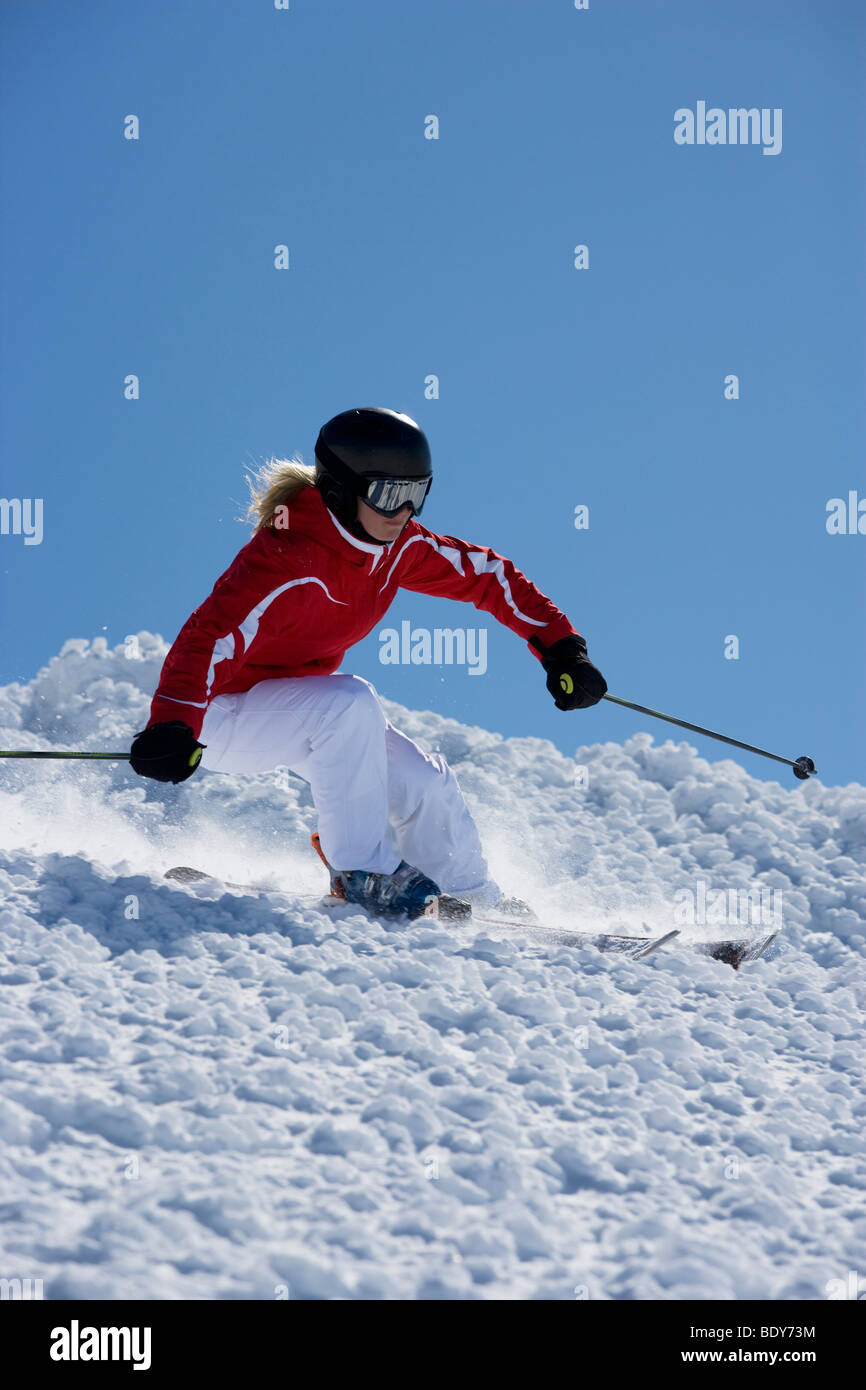 Girl in red carving off piste. - Stock Image