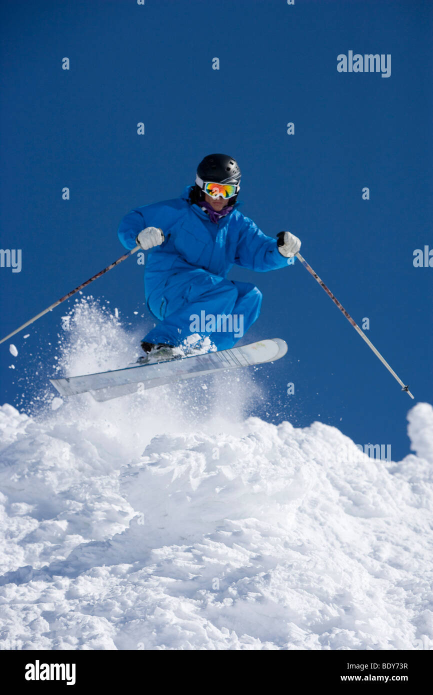 Man in blue jump-suit skiing. - Stock Image