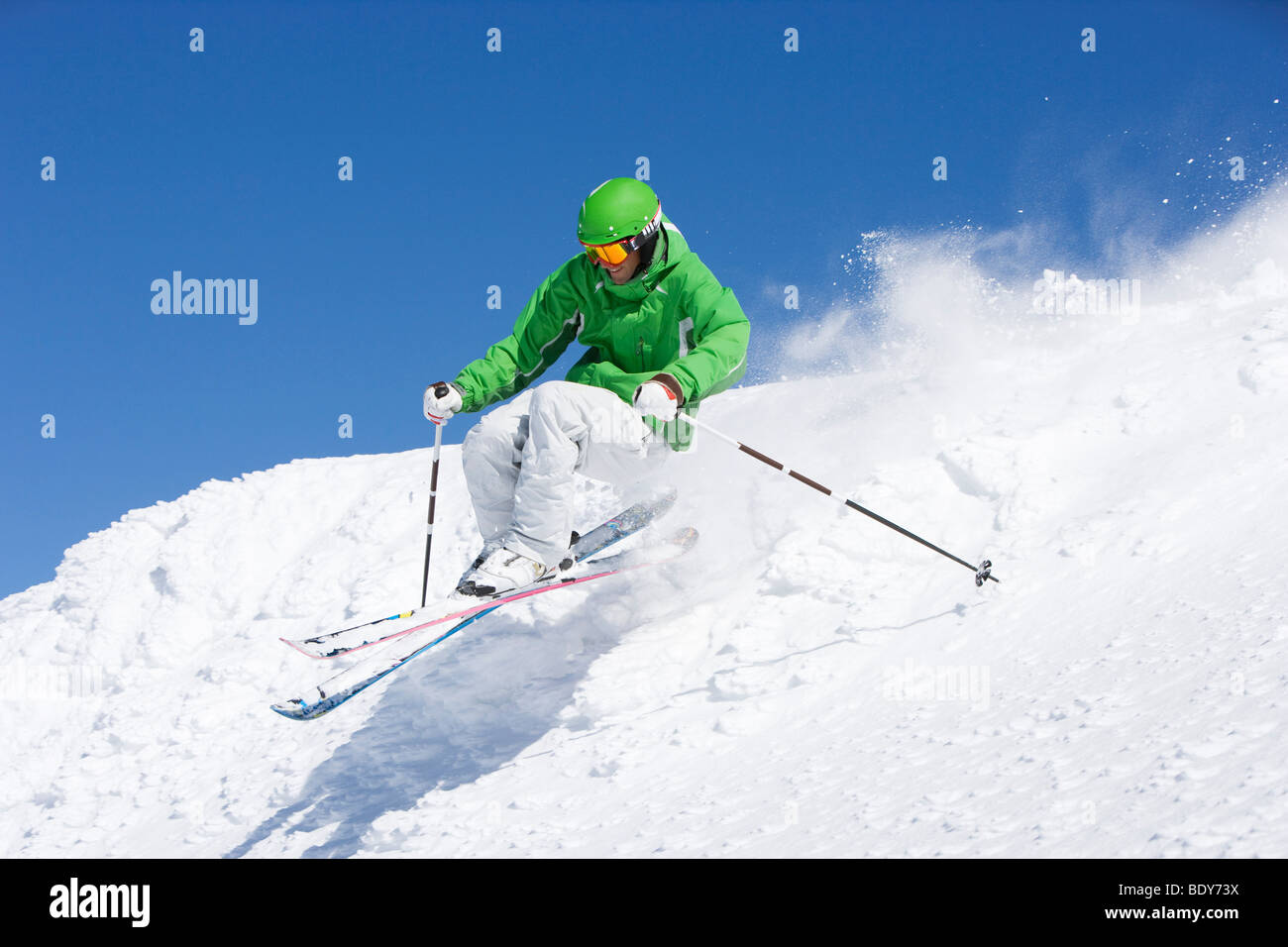 Man in green skiing off piste. - Stock Image
