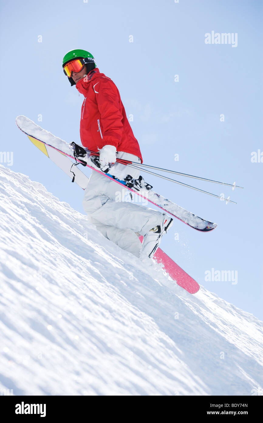 Man sin red carrying skis uphill. - Stock Image