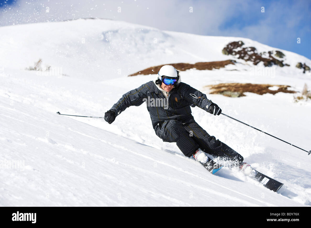 Man in black suit carving off piste. - Stock Image