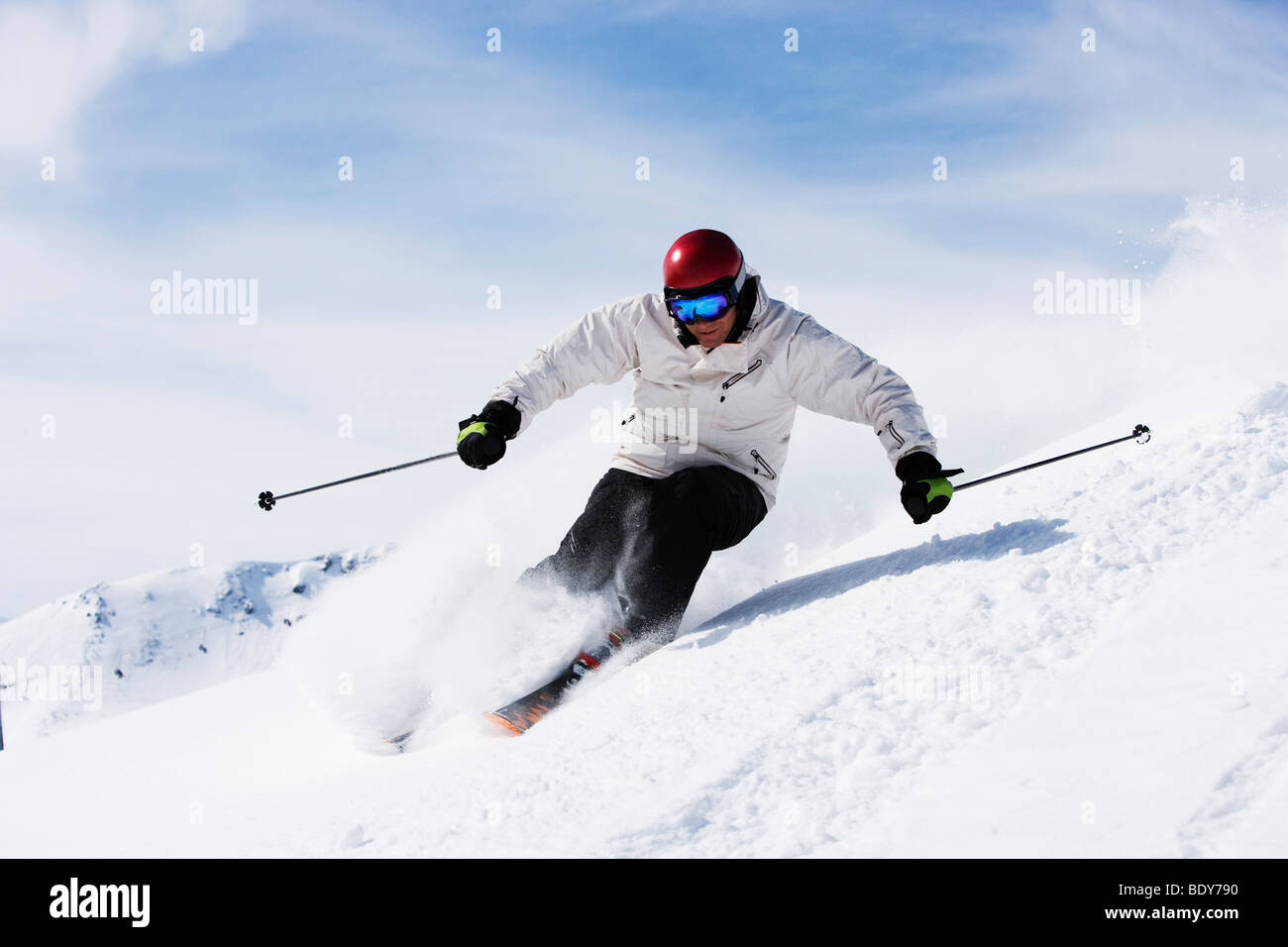 Man in white with red helmet off-piste. - Stock Image
