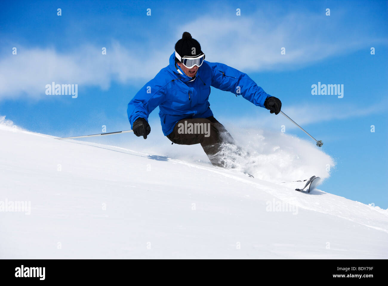 Man in blue & black outfit turning. - Stock Image
