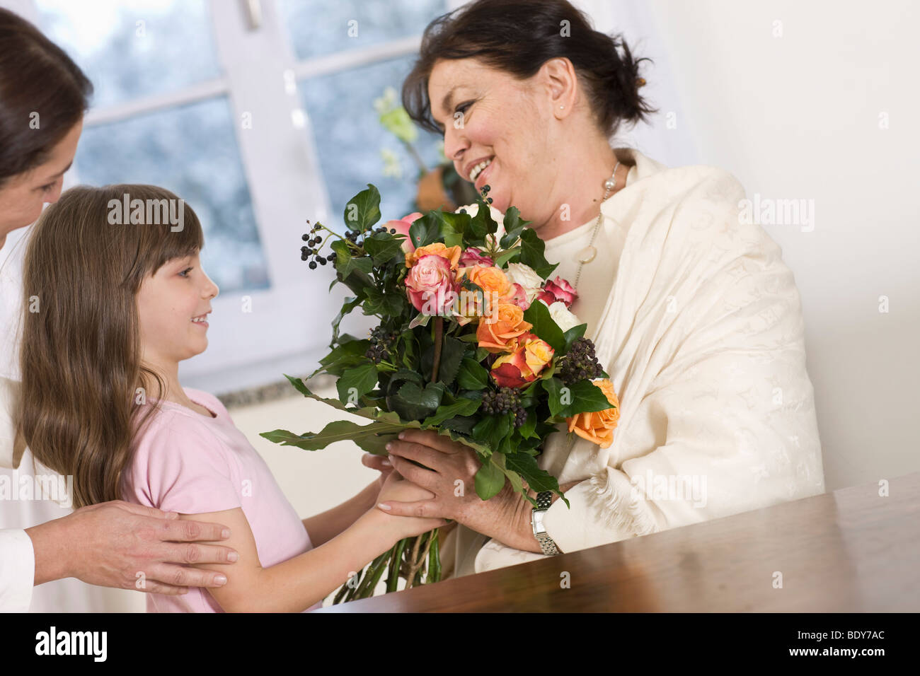 Child giving her grandmother flowers - Stock Image