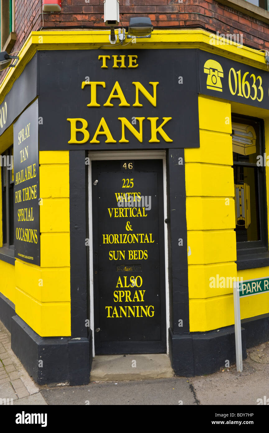 Exterior of yellow and black THE TAN BANK tanning salon in former bank building UK - Stock Image