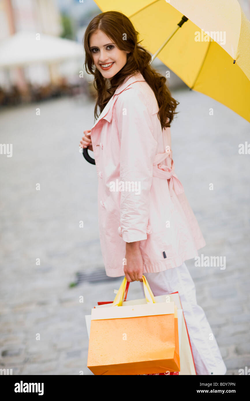 girl goes shopping in the rain Stock Photo