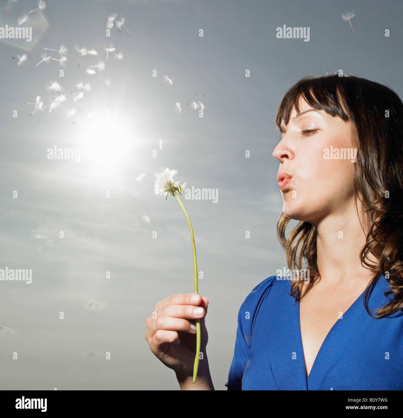 Woman blowing dandelion Stock Photo