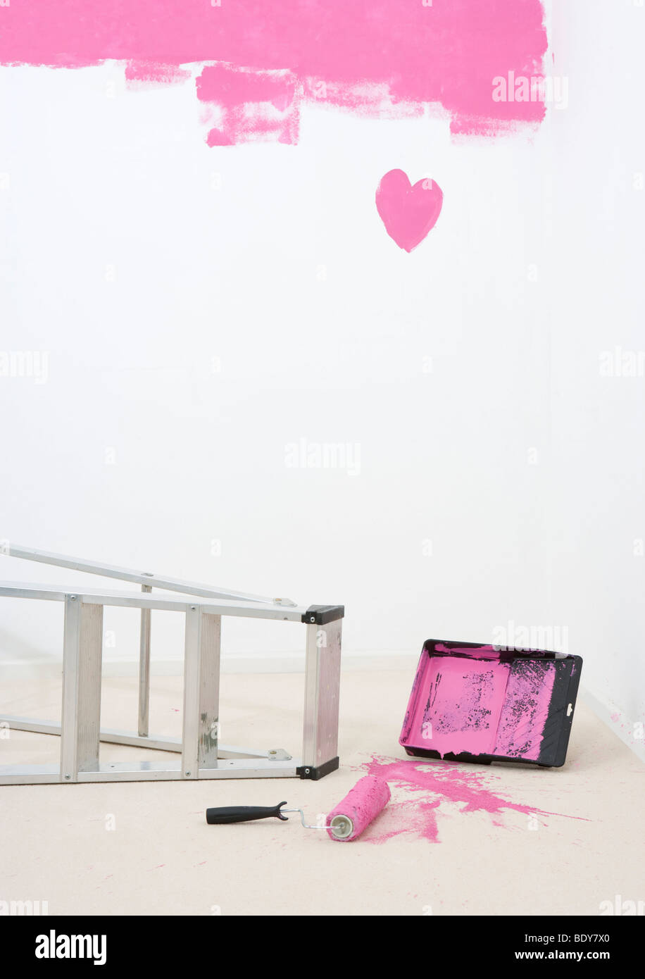 painted heart on wall and spilt paint - Stock Image