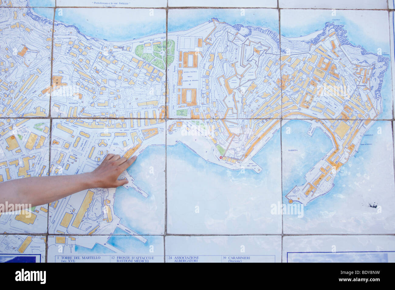 Man pointing with finger on tiled map - Stock Image