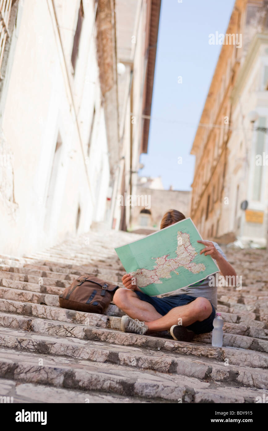 Man sitting on stairs reading map - Stock Image