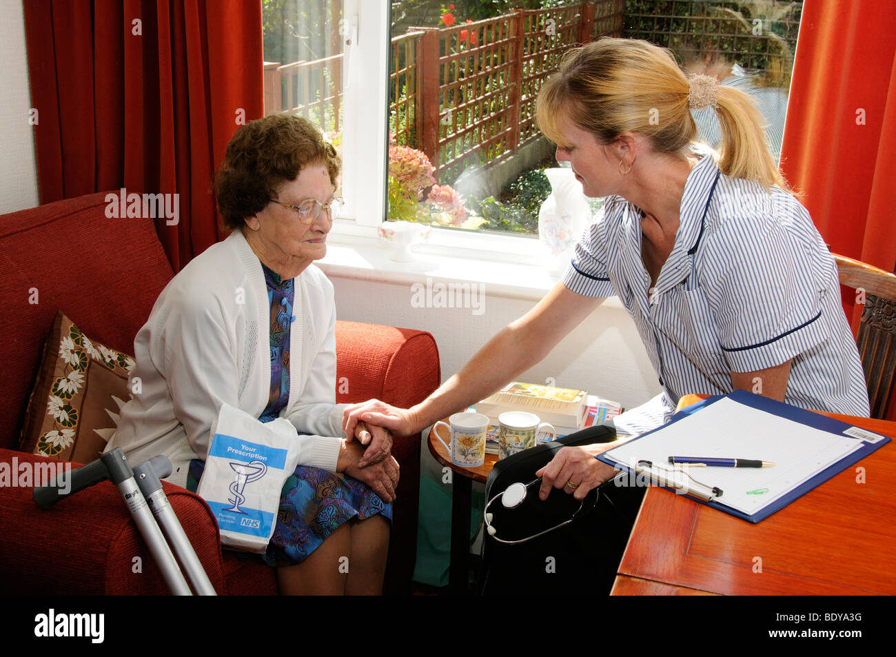 Nursing care with the elderly nurse visiting an elderly woman in her home - Stock Image