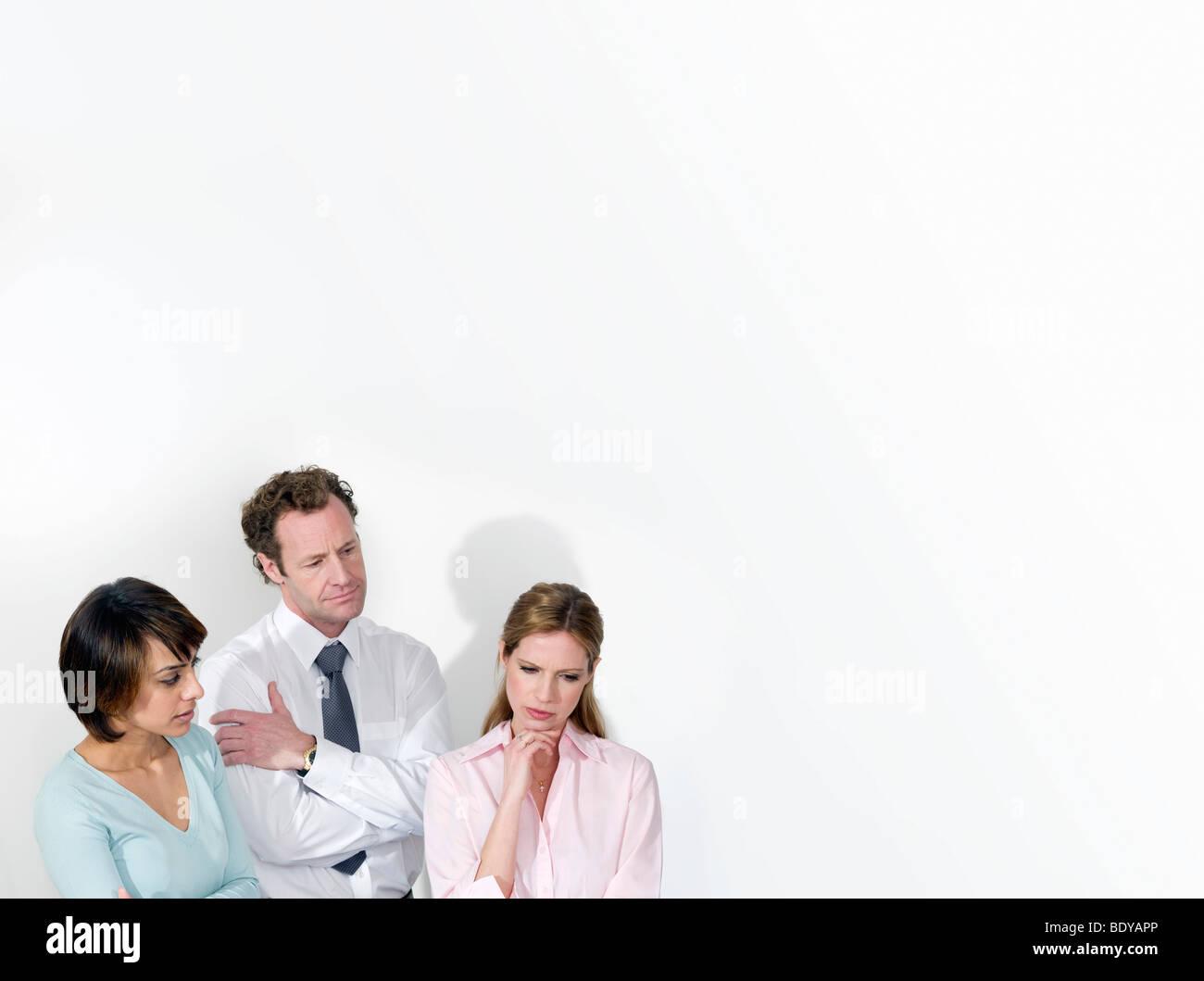 A business trio deliberating - Stock Image