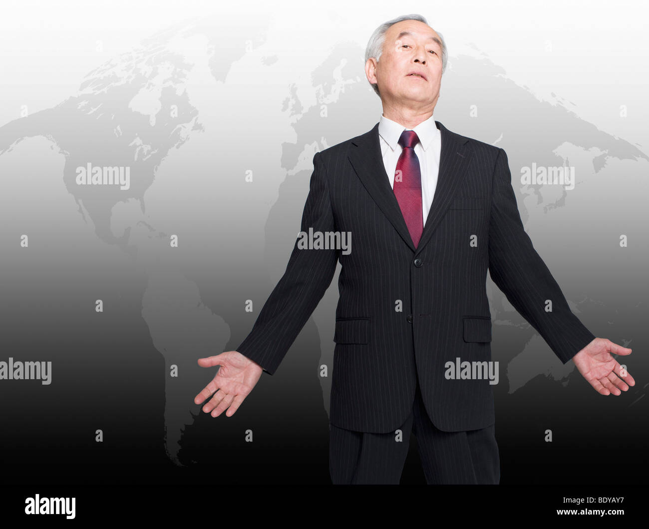 Asian man standing in front of world map - Stock Image