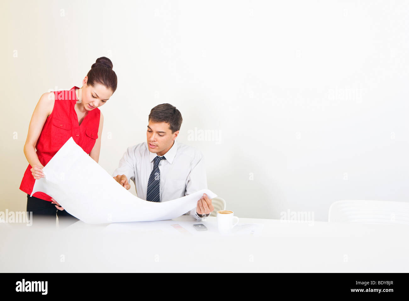 Two colleagues conferring over plans Stock Photo