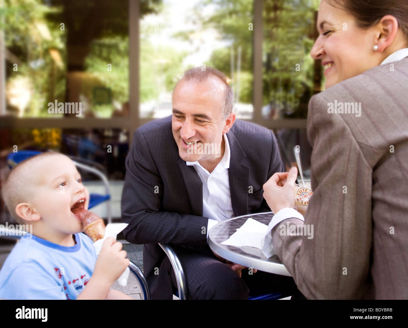 business couple with son in outdoor cafe - Stock Image