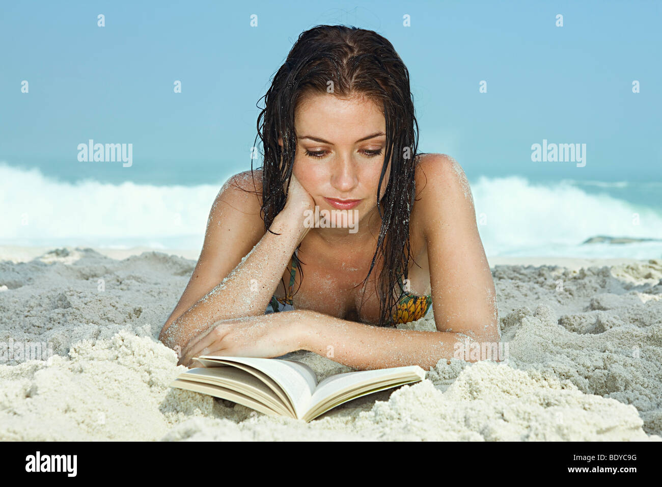 Young Women on Beach reading a book - Stock Image
