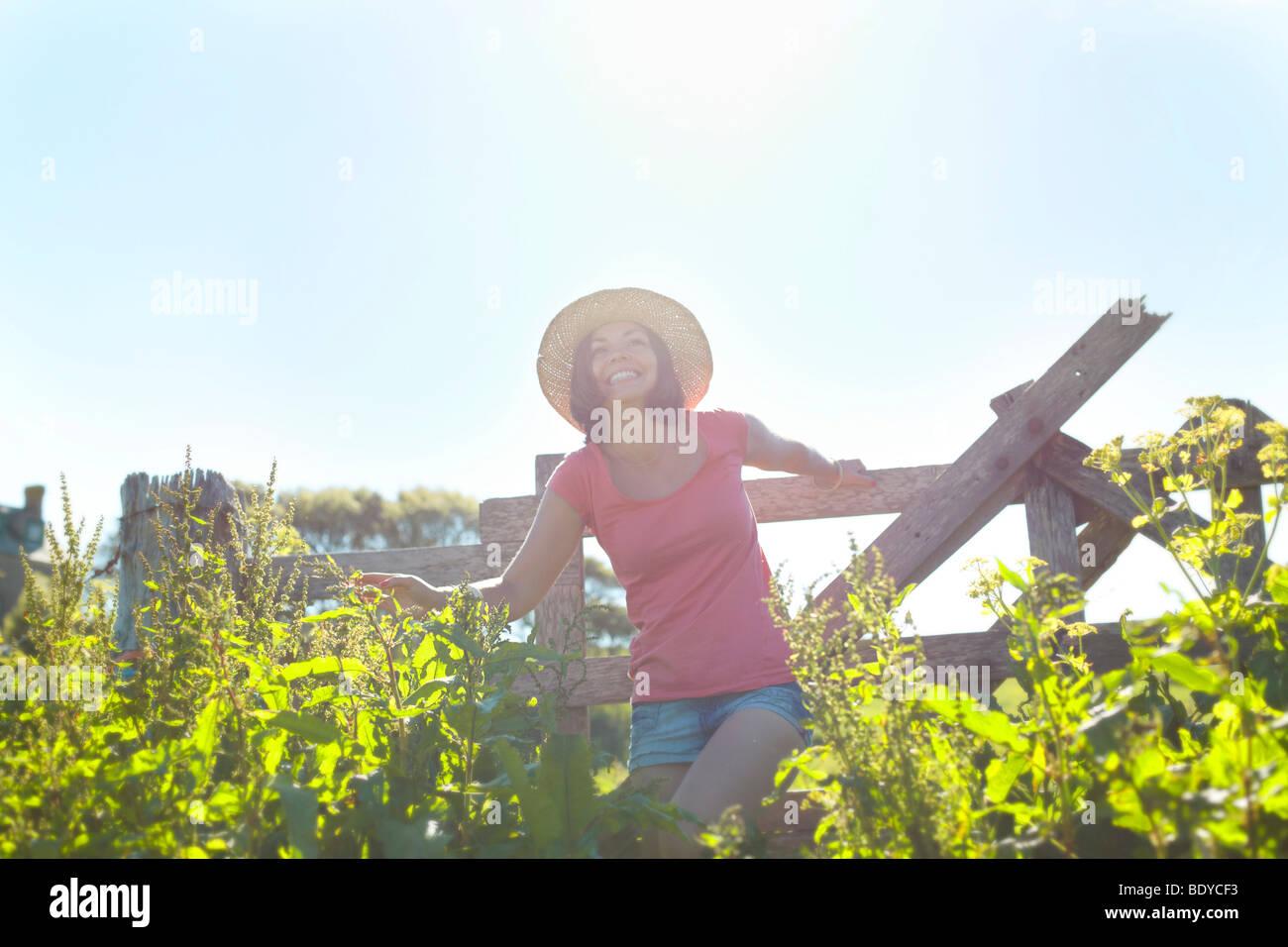 A girl climbing over a fence - Stock Image