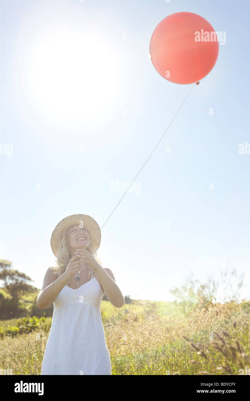 A girl in a field with a red balloon - Stock Image