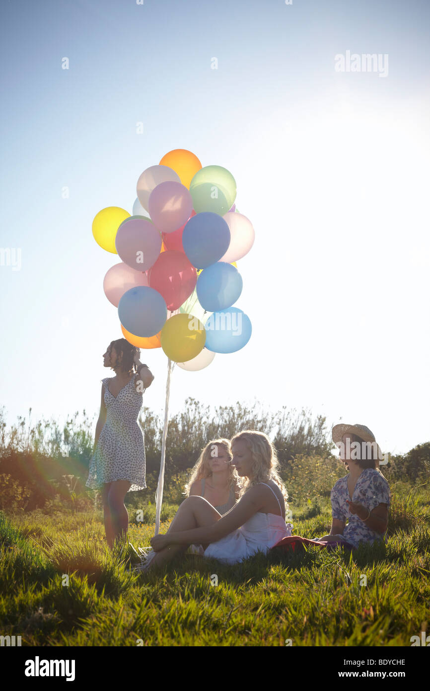 four girls in a field with balloons - Stock Image