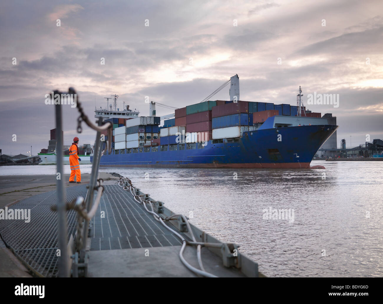 Port Worker And Ship Coming Into Port - Stock Image