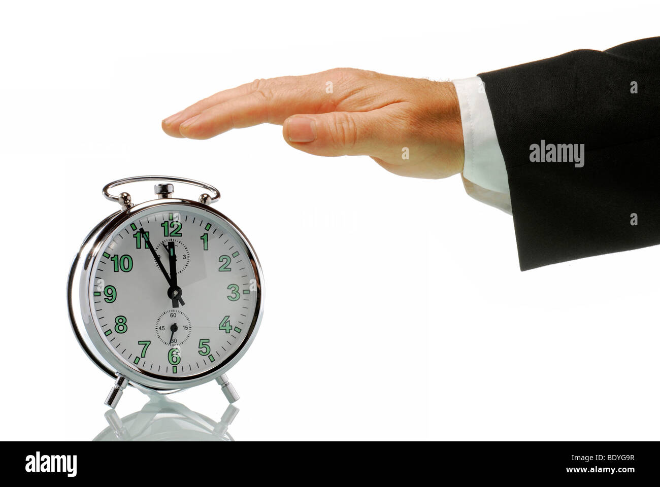 Business man's hand with an alarm clock set at 5 to 12, just before high noon, symbolic image for action in - Stock Image