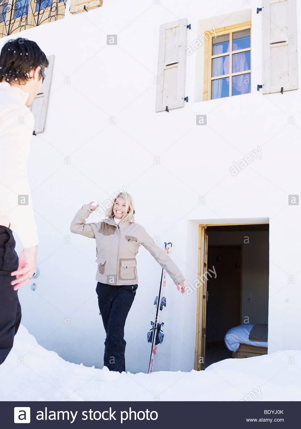 woman and man snowball fight - Stock Image
