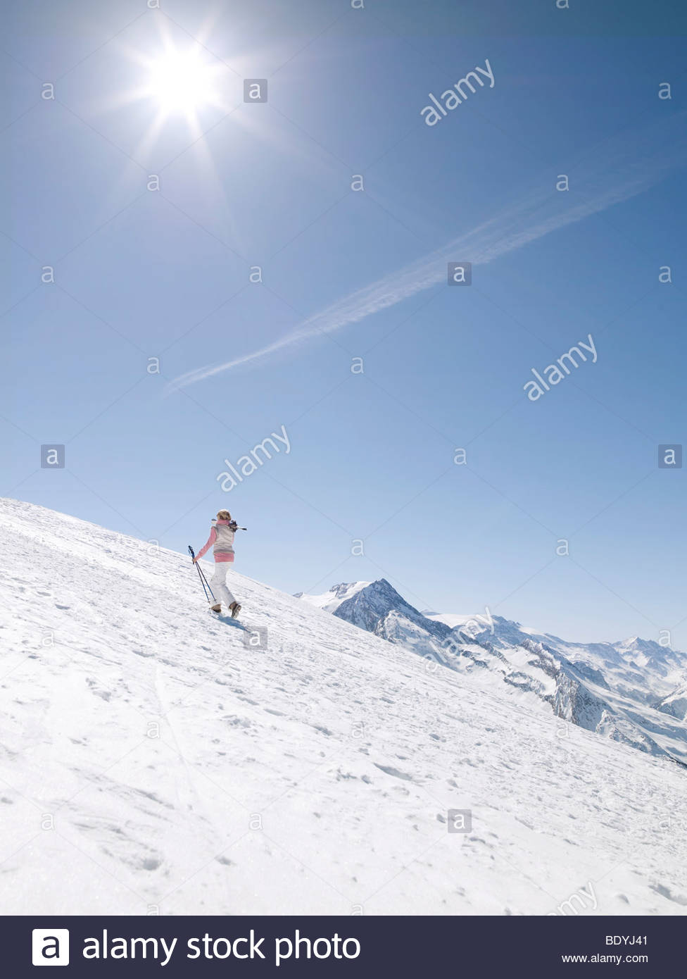 woman walking up mountain with skis - Stock Image