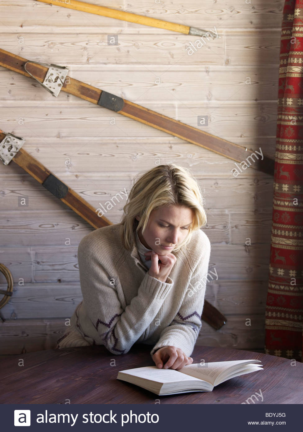 woman reading in ski lodge table - Stock Image